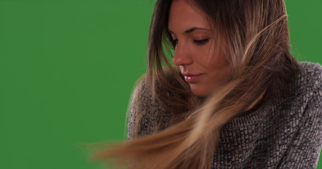 Close up of beautiful millennial woman with hair blowing in wind on greenscreen