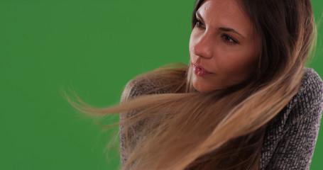 Close up of beautiful millennial girl with hair blowing in wind on green screen