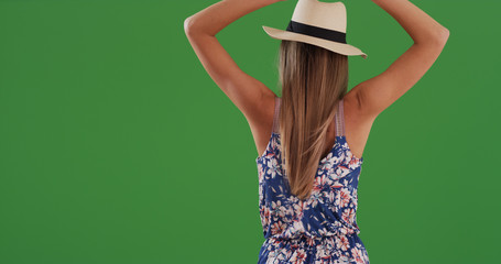 Rear view of woman with arms outstretched feeling the wind on greenscreen