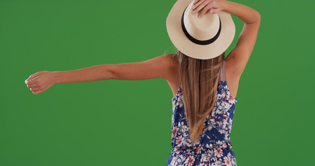 Rear view of woman with arms outstretched enjoying breeze on greenscreen