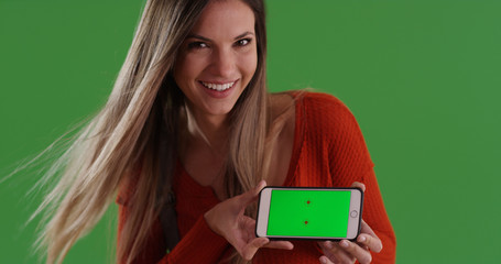 Caucasian girl showing mobile device with green screen display on green screen