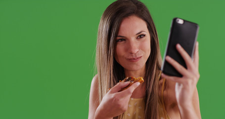Young millennial white woman taking selfie while eating pizza on green screen