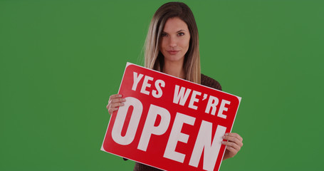 Attractive millennial woman holding sign reading Yes We're Open on green screen