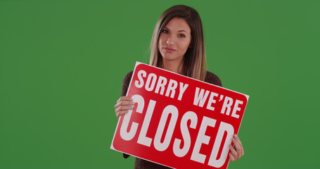 Millennial woman holding sign reading Sorry We're Closed on green screen