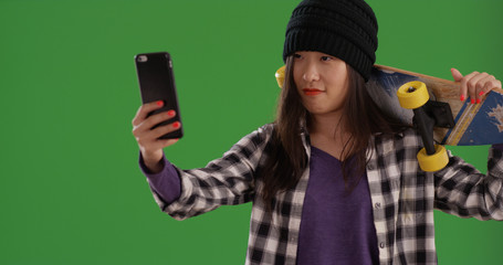 Young Asian female skateboarder taking selfie with phone on green screen