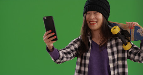 Portrait of happy skater girl taking selfies with smartphone on green screen