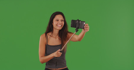 Millennial girl using phone with selfie-stick to take selfie on green screen