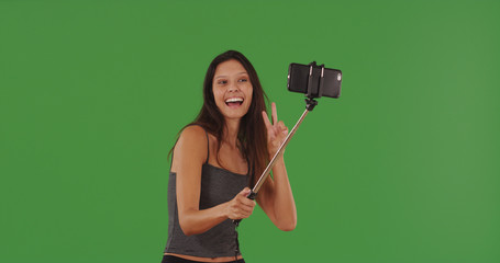 Cute female using smartphone with selfie-stick to take pictures on green screen