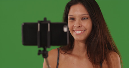 Portrait of lovely female with smartphone on selfie stick on green screen