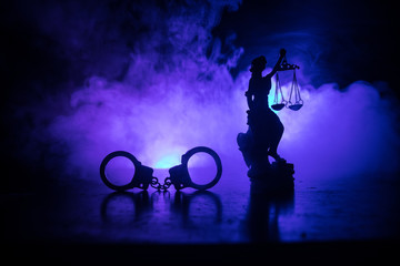 Legal law concept. Silhouette of handcuffs with The Statue of Justice on backside with the flashing red and blue police lights at foggy background.