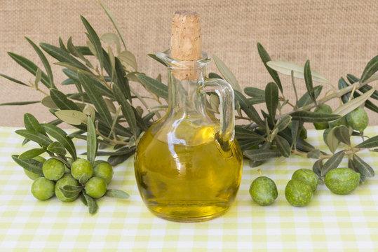 Jarra con aceite de oliva virgen extra, una rama con aceitunas
