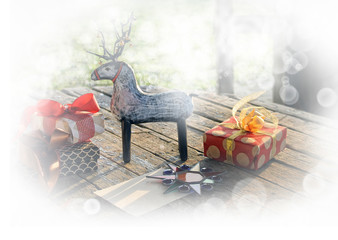 a New Year and Christmas card, a toy wooden deer, a gifts with ribbons,a star and empty blank on the old wooden table