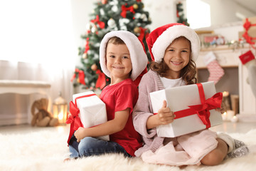 Cute little children in Santa hats with Christmas gift boxes at home