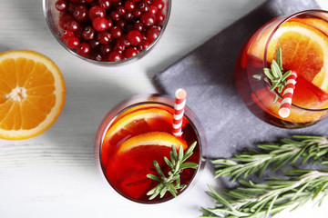 Flat lay composition with cranberry and rosemary cocktail on light table
