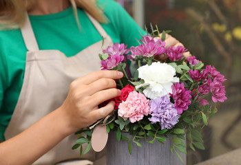 Female florist making beautiful bouquet in flower shop, closeup