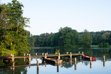 Jetty with rowing boats at the first rays of sunshine. Location: Germany, North Rhine Westphalia, Hoxfeld