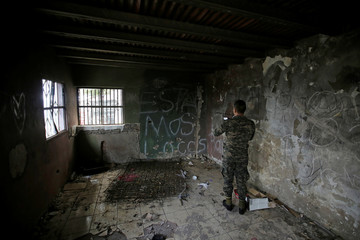 A soldier films a gang safehouse during an anti-gang search operation at the Picachito neighborhood in Tegucigalpa