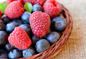 Freshly picked organic raspberries and blueberries in a basket on a burlap cloth background.Blueberry and raspberry. Healthy eating,summer fruits or diet concept.Selective focus.