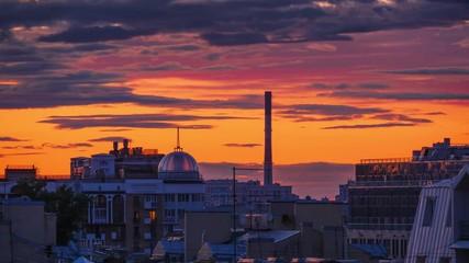 Fotobehang - Old factory smokestack in city skyline over epic sunset sky background. 4K UHD Timelapse.