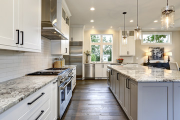 Beautiful modern kitchen in luxury home interior with island and stainless steel chairs
