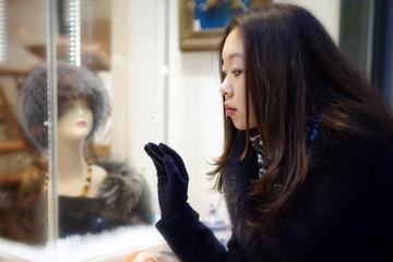 Beautiful Asian girl looking at shop window