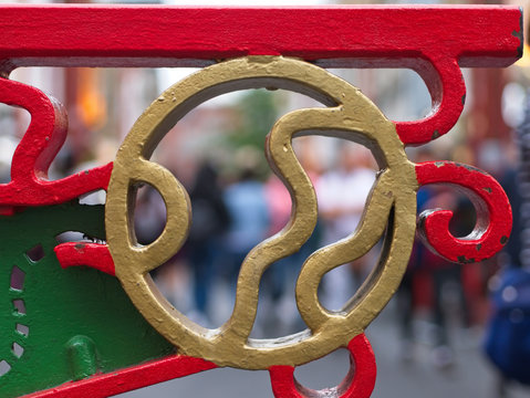 Close-up of Chinese ornamental metal gate painted in gold, red and green. Abstract image of Chinatown.