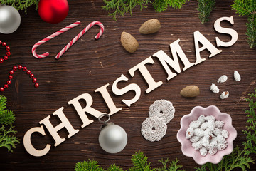 "sweet decoration and the word ""christmas"" on wooden background"