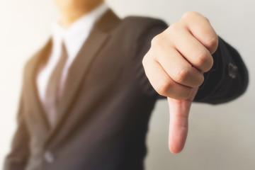 Businessman hand showing thumb down sign gesture. Dislike or bad concept