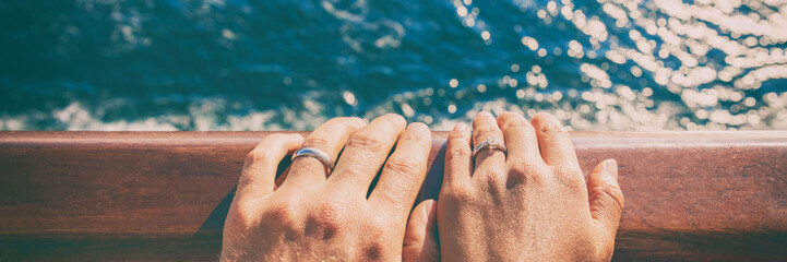 Wedding bands newlyweds couple on honeymoon travel on cruise ship boat. Closeup of hands against ocean sea background. Panoramic banner.