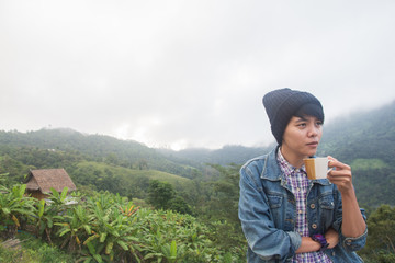 Asian man in Jean jacket And wear black hat,Are smiling holding cup of hot coffee in morning winter season on Mountain Doi Luang Chiang Dao Chiang Mai Thailand