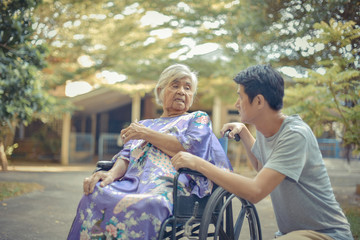Senior woman with daughter; Nurse taking care of senior woman on wheelchair