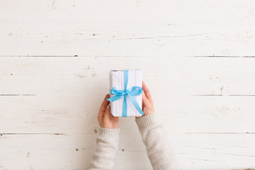 Top view on young woman's hands holding Christmas, birthday or any other celebration gift wrapped in white paper on white wooden background. Preparing for holidays and celebration.