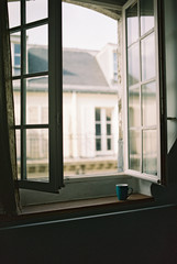 Cup of coffee on windowsill looking out at Paris, France street
