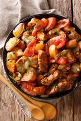 Ojahuri fried meat with potatoes, tomatoes, herbs and spices close-up on a frying pan. Vertical top view