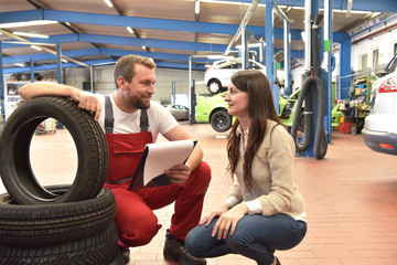 Beratungsgespräch in der Autowerkstatt zum Reifenwechsel - Mechaniker und Kundin im Autohaus // Consultation in the car repair shop to change tyres - mechanic and customer in the car dealership