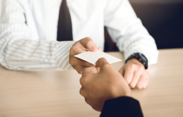 Two businessmen exchanged white business cards on a wooden table in office.