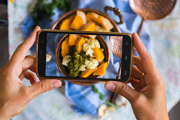 Woman hands takes photography of food on table with phone. Dinner, lunch. Cooked steam vegetables. Smartphone photo for social networks or blogging post. Vegetarian, healthy, organic
