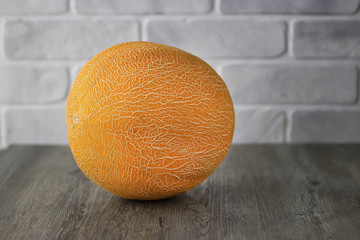 Ripe yellow melon on gray wooden table.