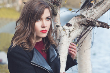 Autumn portrait of cute woman with healthy hair and makep walking in fall park outdoors