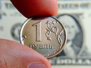 Fingers hold the Russian coin 1 ruble against the background of a dollar note. Close-up