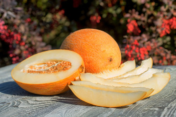 Whole and sliced melon on wooden table outdoors