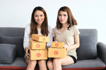 Cheerful Asian entrepreneur owner women with cardboard box sitting on modern sofa at home. Online start up business.