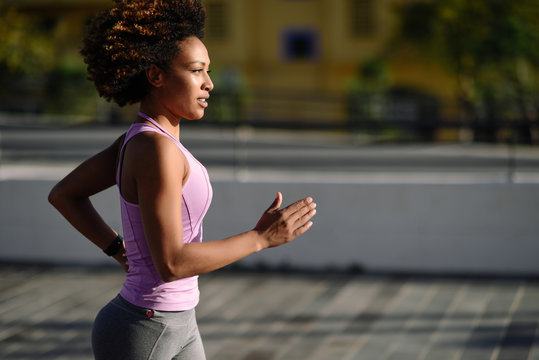 Black woman, afro hairstyle, running outdoors in urban road.