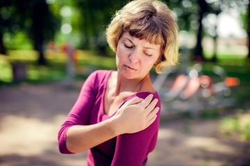 Young woman feeling pain in her shoulder, neck during sport workout in the park. Sport, medicine and people concept