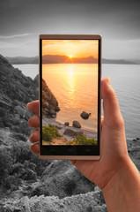 Sunrise over the sea on a screen of smartphone