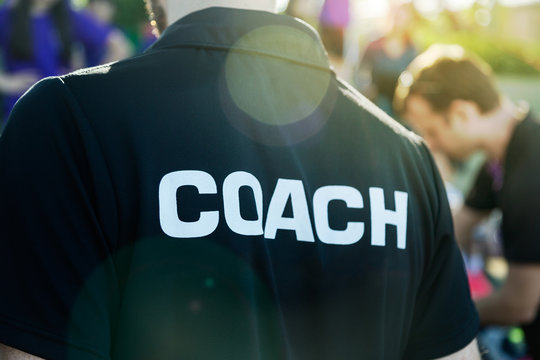 Sport coach in black shirt with white Coach text on the back standing outdoor at a school field, with morning lens flare