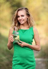Kobieta w zielonej sukience trzymająca kubek z wodą,  mięta i cytryną
