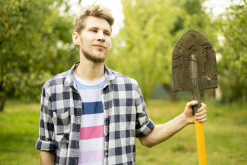 portrait of young happy farmer carrying shovel on a summer agriculture eco farm a