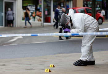 A police officer photographs evidence in the town centre after reports of a stabbing in Barnsley
