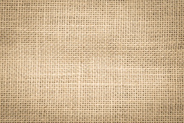 Hessian jute sackcloth woven burlap texture background in sepia cream old aged brown color